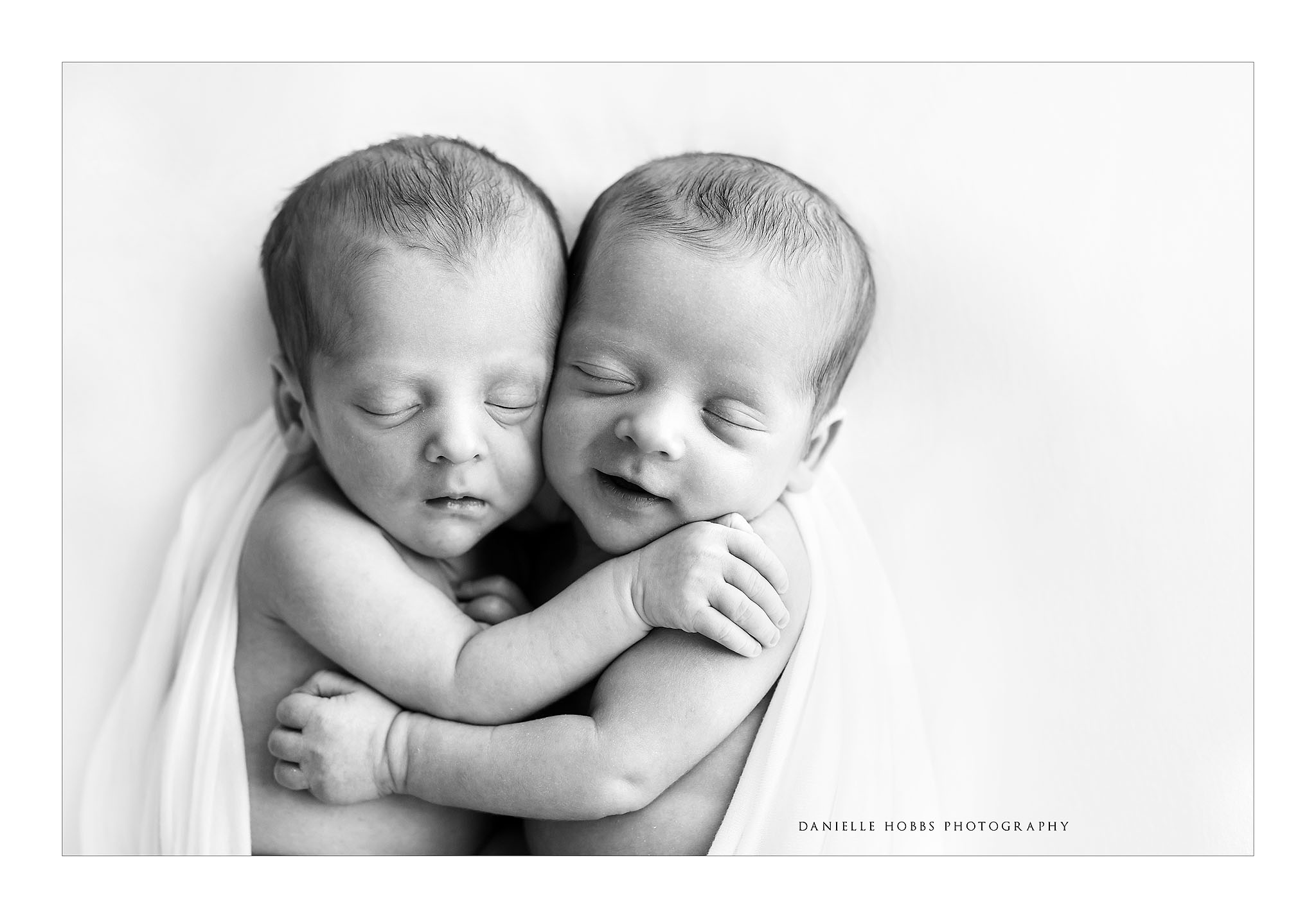 Identical twin boys with parents hands newborn twins hugging